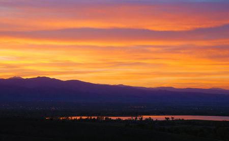 Colorful and spectacular sunset over purple mountains' majesty, reflected brightly in a distant lake.