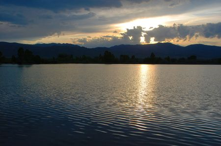 descends: A dreamy sunset descends over a small lake and distant western mountains Stock Photo