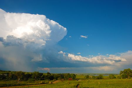 Thunderhead towers over a warm pastoral scene