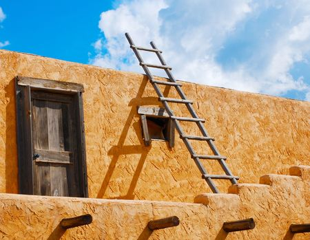 adobe pueblo: Ladder on a Southwest-style stucco building in New Mexico Stock Photo