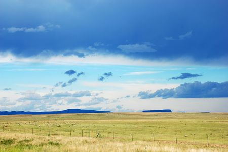 mesas: Green field and distant blue mountains under a threatening sky
