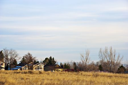 Home on the edge of a field on a bright winter day with bare trees photo