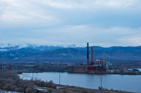 Night falls over a view of a power plant and town in Colorado