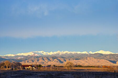 Yellow sunrise on snow-capped Rocky Mountains in Colorado photo