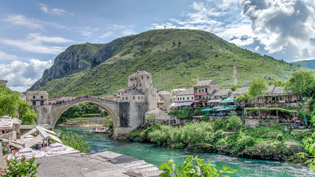 Mostar, Bosnia Herzegovina - May 1, 2014: Stari Most bridge and the cross on the hill in Mostar