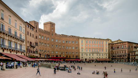 Siena, Italy - September 5, 2014: Tourists enjoy Piazza del Campo square in Siena, Italy. The historic centre of Siena has been declared by UNESCO a World Heritage Site. Editorial