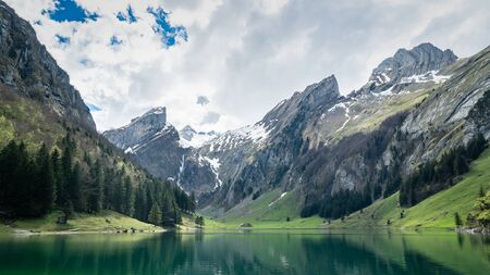 Seealpsee, Switzerland - May 2017: Seealpsee lake with the Swiss Alps (mountain Santis) in the background, Appenzeller Land, Switzerland