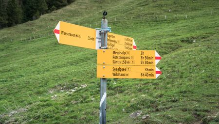 Seealpsee, Switzerland - May 2017: Yellow sign post with mountains in the Swiss Alps.