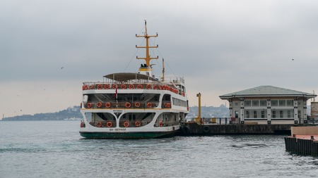 Istanbul, Turkey - December 2017: Istanbul ferry at Besiktas pier to get passengers on a cloaudy and rainy day, Istanbul, Turkey