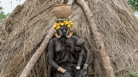 Mago National Park, Omo River Valley, Ethiopia - September 2017: Portrait of a Mursi woman. The women of the Mursi tribe have a lip plate and iron decorations