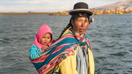Puno, Peru - September 2017: Unidentified woman and her baby at the Floating island Isla Flotante, Titicaca lake, Peru