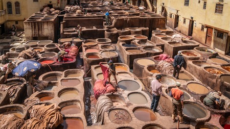Fez, Morocco - April 2018: Men working as tanners in the dye pots at leather tanneries viewed from from the Terrace de Tanneurs in the ancient medina, Fes el Bali, in Fez, Morocco.