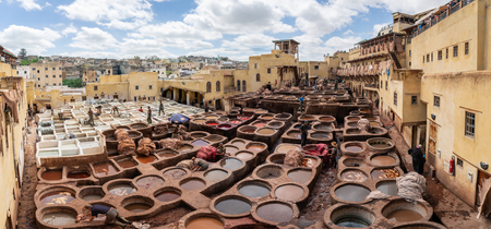 Fez, Morocco - April 2018: Leather dying in a traditional tannery. Men working as a tanners in the dye pots at leather tanneries viewed from from the Terrace 報道画像