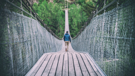 Switzerland, May 2017: Man walking down in Goms Hanging Bridge in Switzerland Editorial