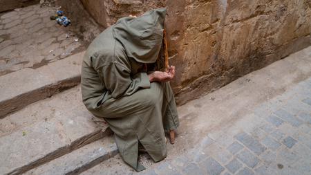 Fez, Morocco - April 2018: Anonymous poor beggar in the street of Fez, Morocco. Banque d'images - 110217777