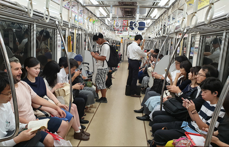 Tokyo, Japan - August 2018: People using smart phones inside subway wagon while riding. Concept of lack of communication in modern society.