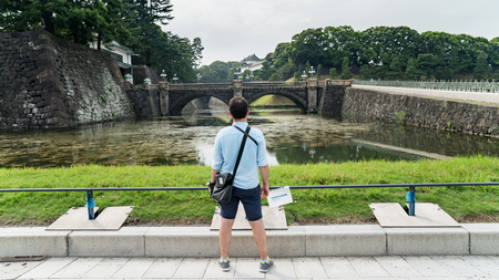 Tokyo, Japan - August 2018: Tourist looking at Tokyo Imperial Palace and Seimon Ishibashi stone bridge of main gate, Japan