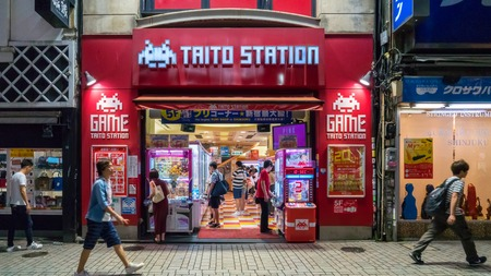 Tokyo, Japan - August 2018: Long exposure photo of Taito station arcade gaming center stands as visitors passes by