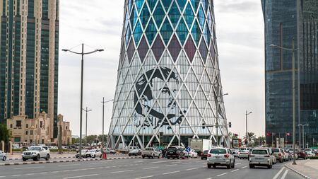 Doha, Qatar - February, 2019: Tornado Tower with image of Emir Tamim bin Hamad al-Thani, iconic glassed high rises in West Bay. Skyscraper of Financial District in Middle East, Persian Gulf.