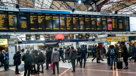 London, United Kingdom - Jarnuary 2019: Passengers looking at the timetable on electronic board in Victoria station is a central London railway terminus and connected to Underground