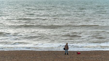 Woman with her dog on the shore of the sea in distance