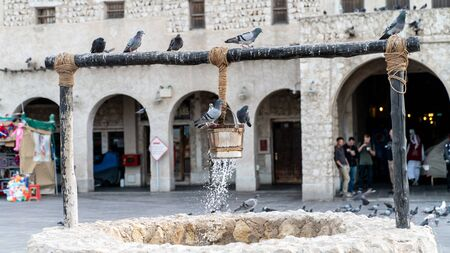Doha, Qatar - February 2019: The old well fountain and pigeons in front of Al Fanar buildings, located in Souq Waqif, Doha, Qatar. Editorial