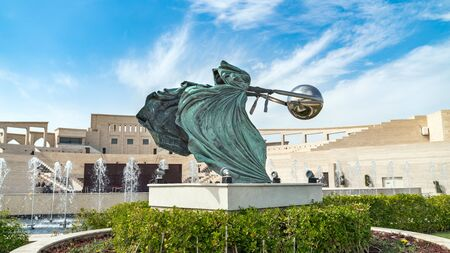 Doha, Qatar- January 2019: Katara Cultural village with statue in foreground and the Amphitheater in the background