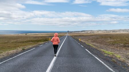 Iceland road landscape with an unidentified woman walking