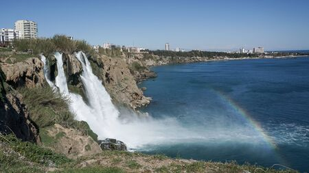 Antalya, Turkey - March 2019: Waterfall Duden falling into the Mediterranean sea with rainbow scene