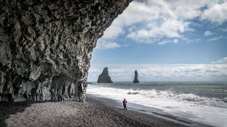 The black sand beach of Reynisfjara, mount Reynisfjall and the volcanic basalt columns in the southern coast of Iceland.