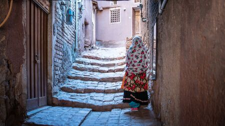 Abyaneh, Iran - May 2019: Unidentified woman with traditional Persian clothes walking down a narrow road