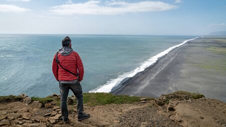Unidentified man overlooking the endless volcanic black sand beach located in Vik Iceland