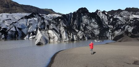 Solheimajokull, Iceland - August 2019: Unidentified man taking a photo by the Solheimajokull outlet glacier and the glacial lagoon