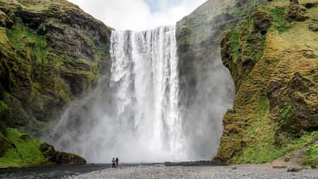 Huge waterfall of Skogafoss with an unidentified couple taking photographs in Skogar, south Iceland