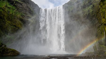Huge waterfall of Skogafoss with a rainbow formed from sun shine in Skogar, south of Iceland 写真素材