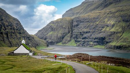 Unidentified man walking towards church from village of Saksun located on the island of Streymoy, Faroe Islands, Denmark 写真素材