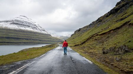 Unidentified man walking in the dramatic road landscape in Faroe Islands