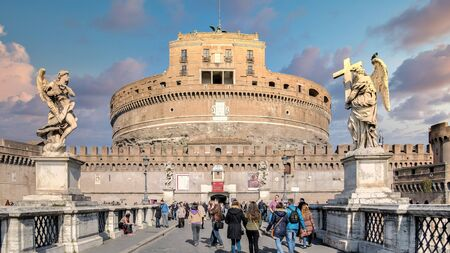 Rome, Italy - February 2015: Saint Angelo Castle and tourists on the bridge over Tiber River. Built by Hadrian emperor as mausoleum in 123AD ancient Roman Empire landmark.