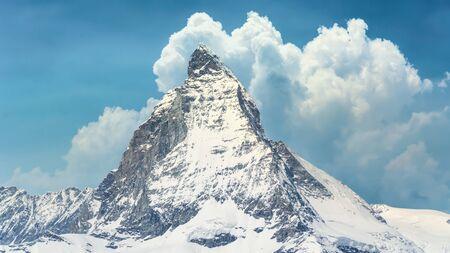 Iconic view of snowy Matterhorn peak with blue sky and clouds, Zermatt, Switzerland