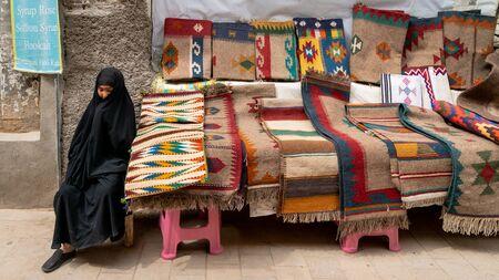 Shiraz, Iran - May 2019: Iranian woman selling kilim and carpets in her stall in Grand Bazaar of Shiraz Redactioneel