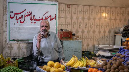 Isfahan, Iran - May 2019: Iranian greengrocer smoking a cigarette while selling fruit in his shop in Grand Bazaar of Isfahan