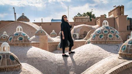 Kashan, Iran - May 2019: Iranian woman on the brick dome roof of Sultan Amir Ahmad Qasemi Bath house Éditoriale