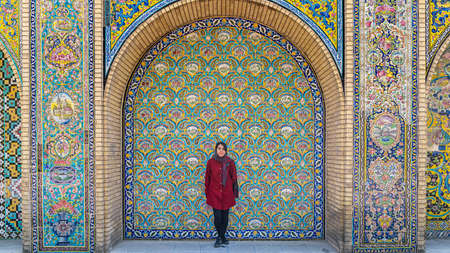 Tehran, Iran - May 2019: Iranian girl standing against a tiled wall in the courtyard of Golestan palace, a UNESCO world heritage site