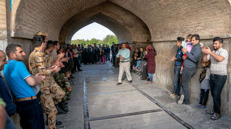 Isfahan, Iran - May 2019: Local Iranian people singing and entertaining themselves under the Khaju bridge over Zayandeh river