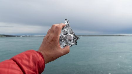 Man holding a piece of ice in Jokulsarlon glacier lagoon formed with melting ice, Iceland. Global warming and climate change concept