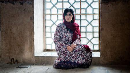Isfahan, Iran - May 2019: Iranian woman sitting by the window in of Ali Qapu Palace in Isfahan Naqsh-e Jahan Square