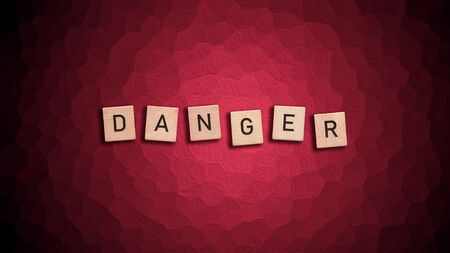Danger written with wooden tiles over red background.