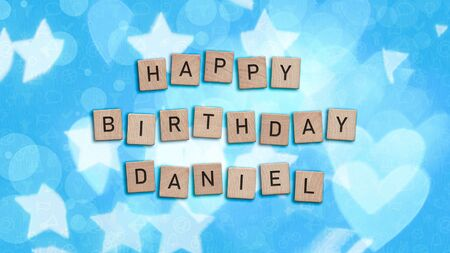 Happy Birthday Daniel card with wooden tiles text. Boys birthday card in blue. This image can be used for a eCard or a print postcard.
