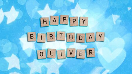 Happy Birthday Oliver card with wooden tiles text. Boys birthday card in blue. This image can be used for a eCard or a print postcard. Stock Photo