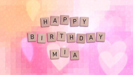 Happy Birthday Mia card with wooden tiles text. Girls birthday card in rainbow colors. This image can be used for a eCard or a print postcard.